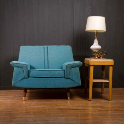 blue chair next to table with a lamp