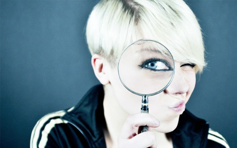 woman holding magnifying glass to her eye